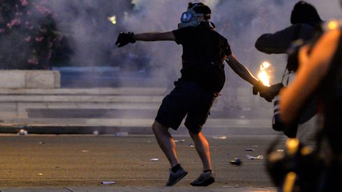 A protester clashes with riot police in front of the Greek Parliament in Athens on July 15, 2015.