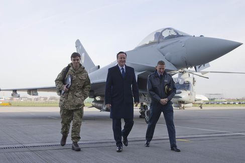 British Prime Minister David Cameron walks past an RAF Eurofighter Typhoon fighter jet during his visit to Royal Air Force station RAF Northolt.