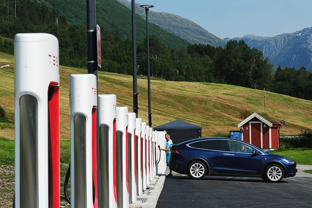 A driver prepares to charge his Tesla car at a Tesla Supercharger charging station in August 2020 in Skei, Norway.