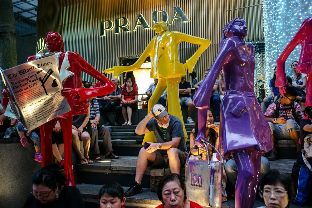 3b6ecb34410d People sit next to sculptures outside a Prada SpA luxury fashion store on  Orchard Road in
