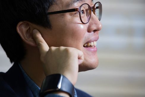 Choi Hyun Chul, chief executive officer of Innomdle Lab, poses for a photograph while wearing the prototype of the TipTalk device with his finger to his ear in Seoul, South Korea, on Oct. 23. Choi, a Samsung Electronics Co. engineer, developed a wristband that keeps eavesdroppers from listening to smartphone conversations.