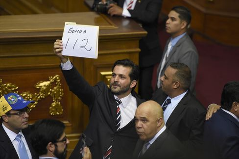 """A deputy holds a sign that reads """"We are 112,"""" in reference to the number of opposition lawmakers who won seats."""