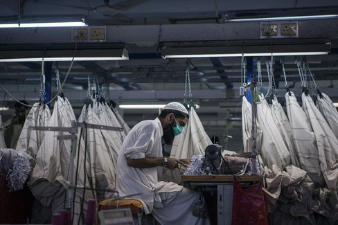 A worker operates a sewing machine at a textile manufacturer in Karachi.