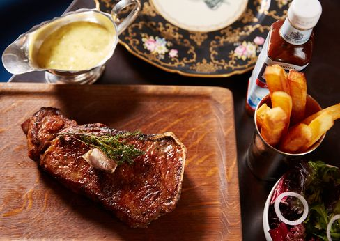 The steaks are served whole, on the bone, with thickly cut French fries and Bearnaise sauce.