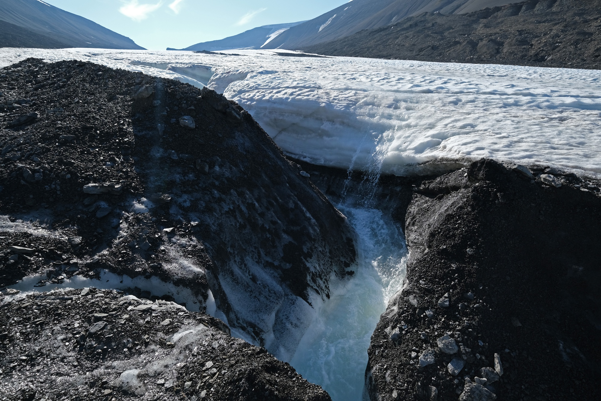 Water flows down from a winding channel on the surface of the melting Longyearbreen glacier during a summer heat wave near Longyearbyen, Norway on July 31, 2020.