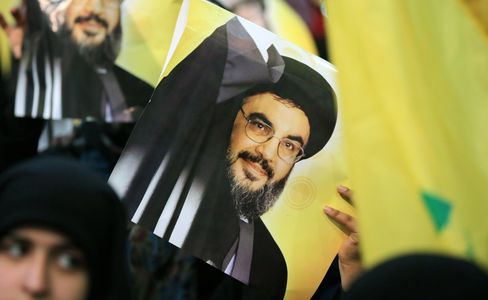 A supporter holds a poster showing Hassan Nasrallah as he addresses supporters in Beirut's southern town of Mujammaa Sayyed al-Shuhada, on Jan. 30, 2014.