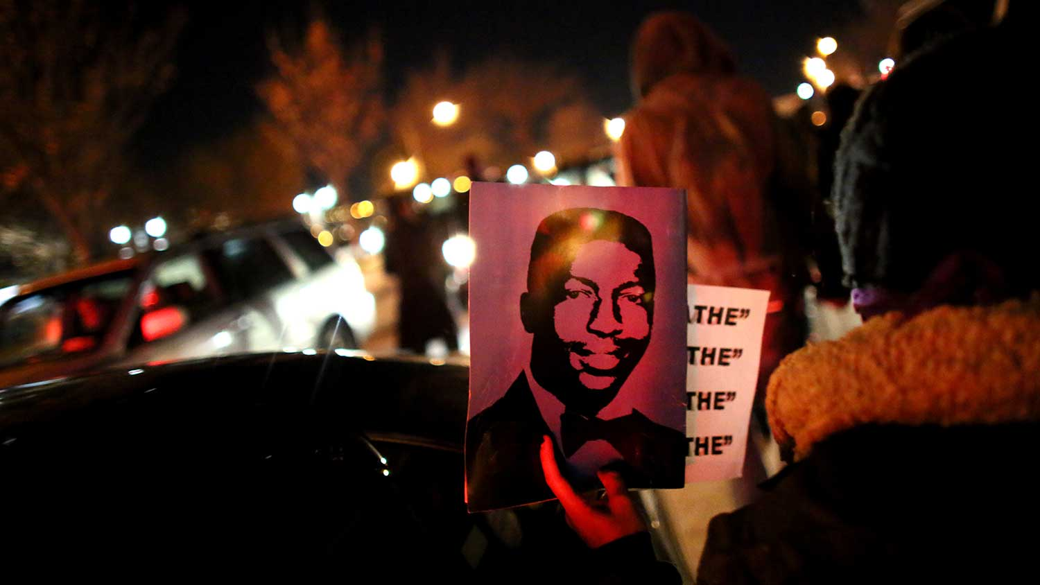 A protester holds up Garner's photo while walking on the West Side Highway following the grand jury's decision on Dec. 3, 2014, in New York.