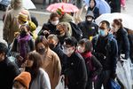 Tourists wearing face masks walk along a shopping street leading to the Sensoji temple in the Asakusa district of Tokyo, Japan, on Tuesday, Jan. 28.