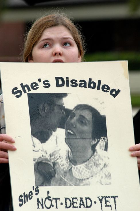 A woman holds a sign supporting Terri Schiavo outside the Florida hospice center where Schiavo stayed in 2005.
