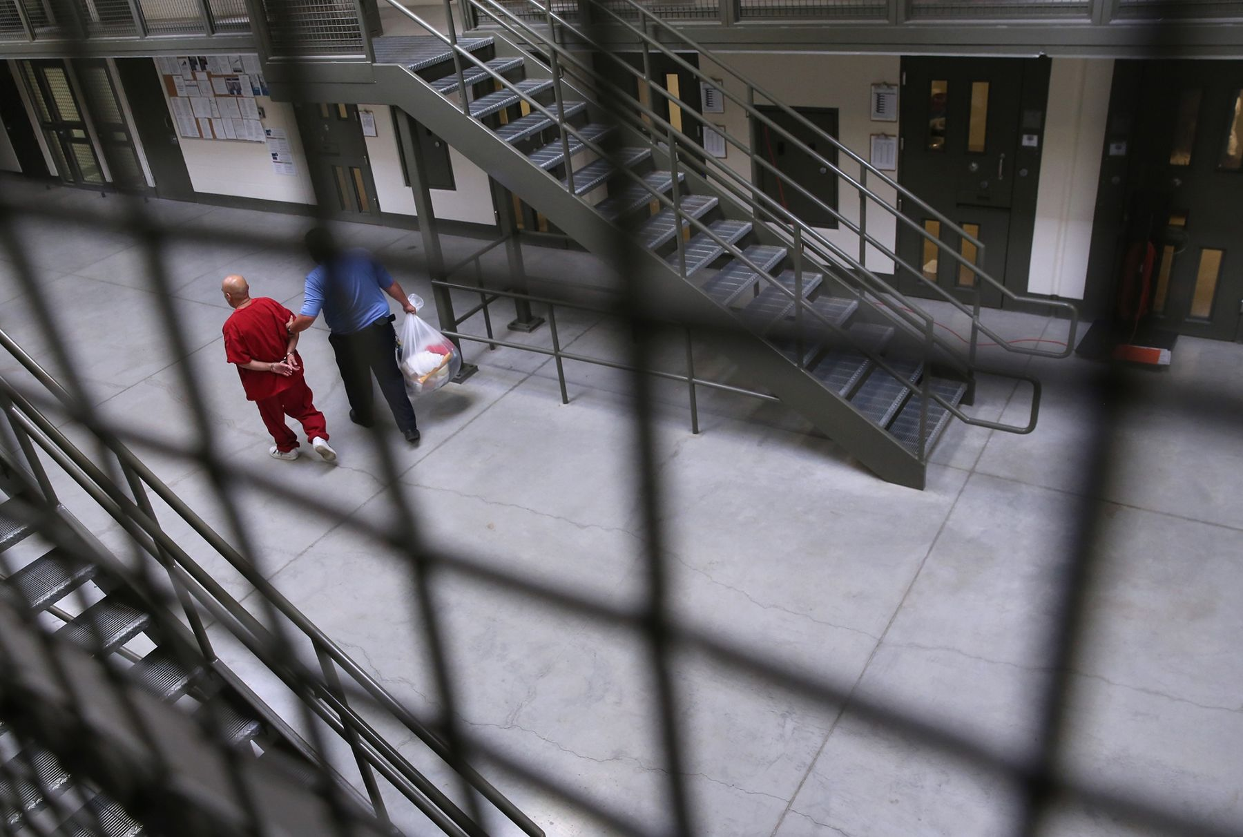 A guard escorts an immigrant detainee at a Geo Group detention facility.