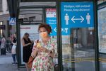 A woman wears a face mask as she waits at a bus stop with an information sign asking people to keep social distance on June 26, 2020 in Stockholm, Sweden.