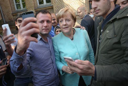 German Chancellor Angela Merkel pauses for a selfie with a migrant before she visited the AWO Refugium Askanierring shelter for migrants on September 10, 2015 in Berlin, Germany.