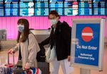 Passengers wear protective masks as they arrive at the Los Angeles International Airport, California, U.S.