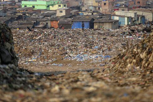 A man walks towards housing at the Deonar landfill site in Mumbai. Photographer: Dhiraj Singh/Bloomberg