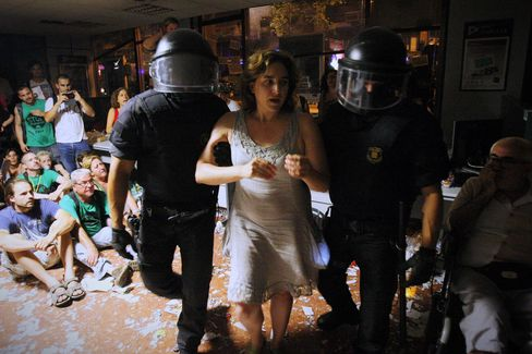 Colau (center) is carried out by police officers after occupying a bank in a protest to support a neighbor facing eviction in Barcelona on July 26, 2013.