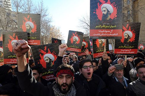 Protesters hold portraits of prominent Shiite Muslim cleric Nimr al-Nimr