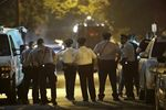 Policer officers watch as a gunman is apprehended following a standoff in Philadelphia.