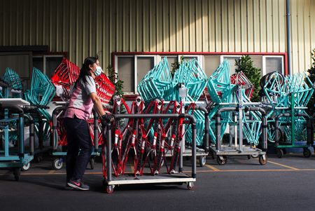 An employee pushes a rack of bicycle frames at the Giant Bicycle factory in Taichung.