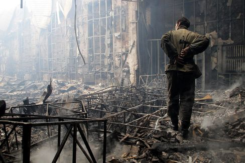 A man looks at a youth culture center damaged during clashes between pro-Russian separatists and Ukrainian forces, in Donetsk on Aug. 28, 2014. Photographer: Alexander Ermochenko/Anadolu Agency/Getty Images