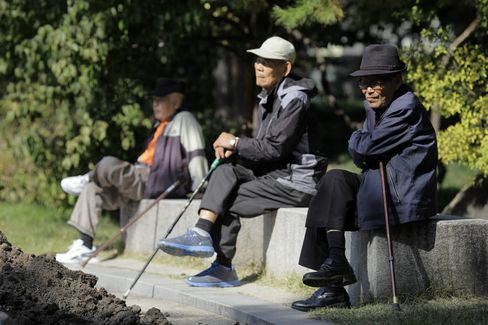 Elderly men sit on benches at Tapgol Park in the Jongro-gu area of Seoul, South Korea.