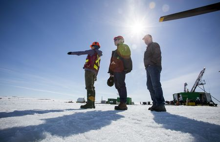 """Atop """"candling,"""" icy snow, CEO Rory Moore (R) of Kennady Diamonds, Chairman Jonathan Comerford (center) and project geologist Martina Bezzola survey their exploration area at the Kennady Kelvin Camp."""