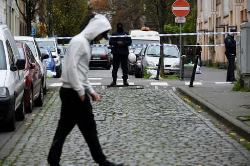 Police officers man a cordon as an operation takes place in the Molenbeek district of Brussels on Nov. 16, 2015.