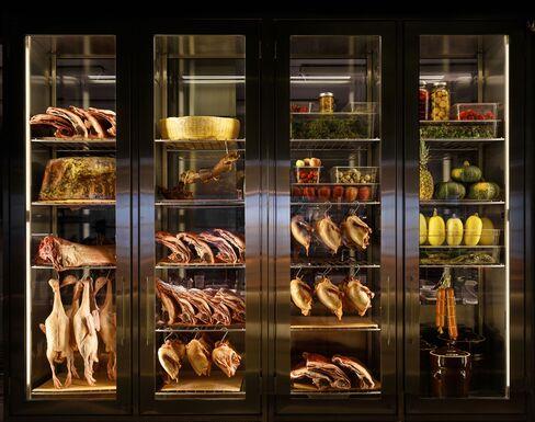 A wallsize fridge, packed with hanging ducks and aging lamb at Momofuku Ko.