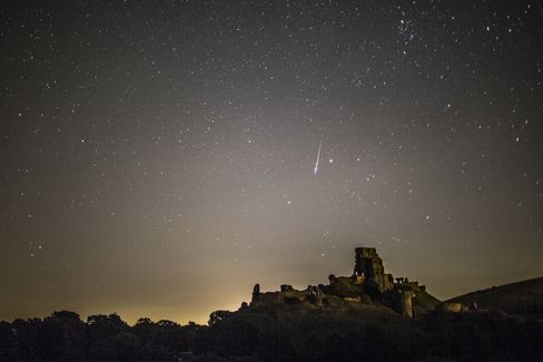 A meteor flashes across the night sky in Corfe Castle, United Kingdom.