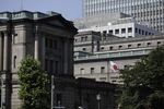 A Japanese national flag flies outside the Bank of Japan (BOJ) headquarters in Tokyo, Japan.