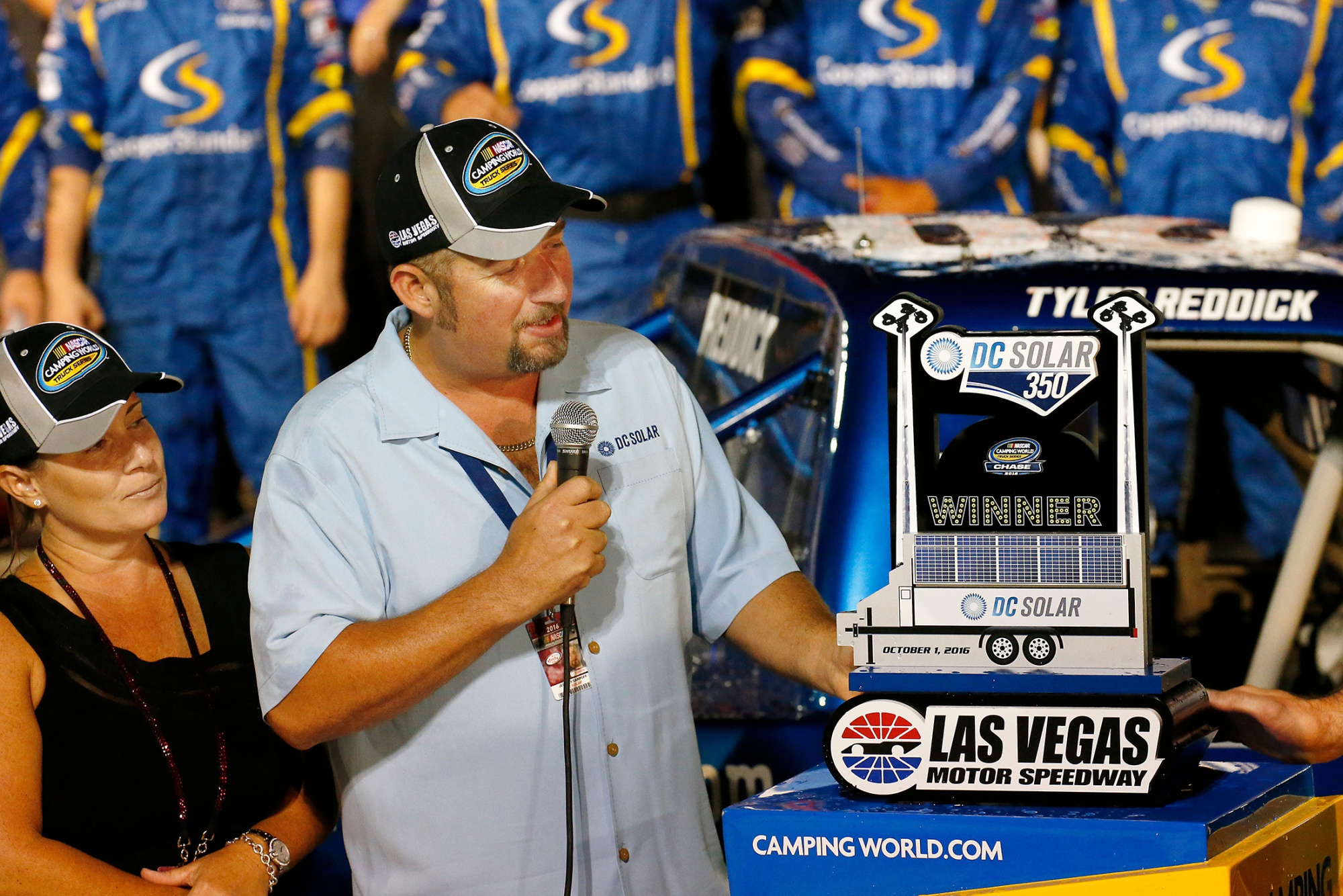 Jeff Carpoff presents a trophy at a racing event.