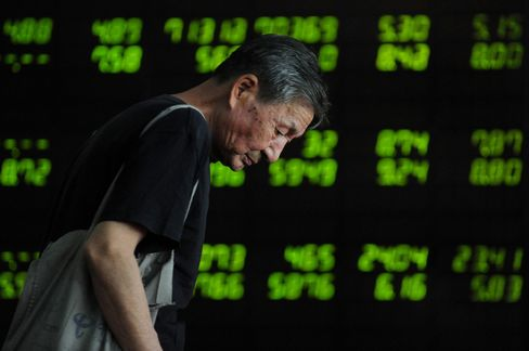 An investor observes electronic board at a stock exchange hall on July 7, 2015 in Shenyang, Liaoning Province of China.