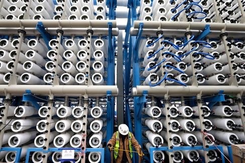 A worker among some of the 2,000 pressure vessels used to convert seawater into fresh water through reverse osmosis in the western hemisphere's largest desalination plant in Carlsbad, California, on March 11, 2015.