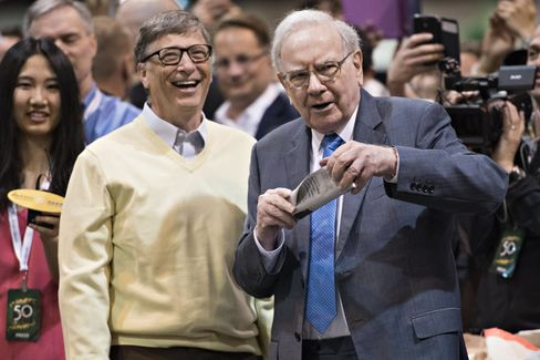 Warren Buffett, Berkshire Hathaway Inc. chairman and chief executive officer, right, talks with Bill Gates, billionaire and co-chair of the Bill and Melinda Gates Foundation, as they tour the exhibition floor during the Berkshire Hathaway Inc. annual shareholders meeting in Omaha, Nebraska, U.S., on Saturday, May 2, 2015. More than 40,000 people are expected Saturday at the Berkshire Hathaway annual meeting, which marks Warren Buffett's 50th year running the company. Photographer: Daniel Acker/Bloomberg *** Local Caption *** Warren Buffett; Bill Gates