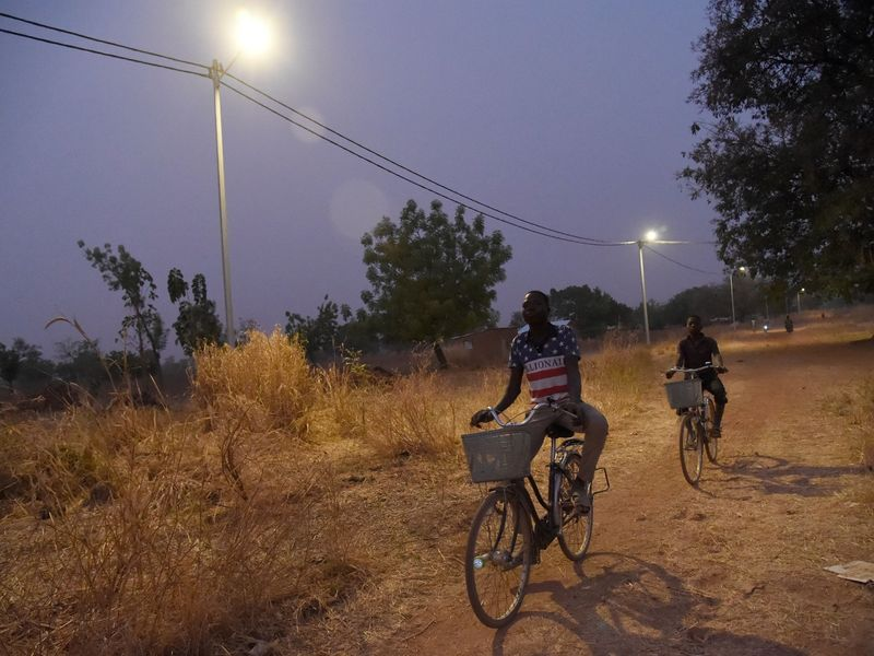 Cyclists ride underneath solar lights in the Takpapieni village in Oti province of northern Togo.