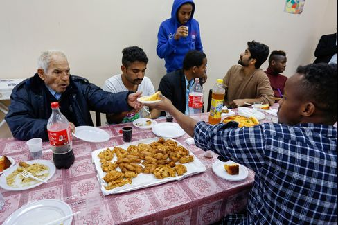 Local residents join refugees for a meal at the Palazzo Condo.