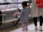 A mother and her children walk through a supermarket in Chiba, Japan.