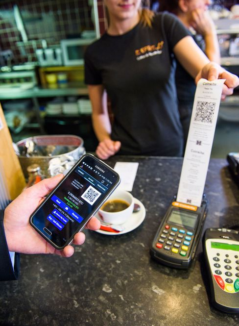 A customer pays for coffee with bitcoins at Java Express.