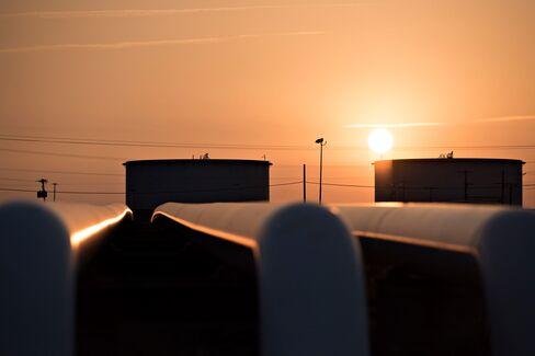 The sun rises beyond oil storage tanks at the Enbridge Cushing storage terminal in Cushing, Okla., on March 25.