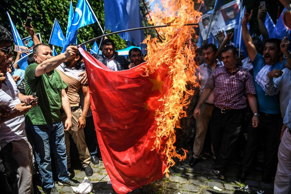 Turkish supporters of the Uighur minority burn a Chinese flag during a protest in 2018.