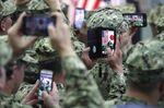U.S. military personnel use smartphones to take photographs of U.S. President Donald Trump and U.S. First Lady Melania Trumpat the U.S. naval base in Yokosuka, Kanagawa Prefecture.