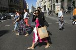 A shopper walks across the street holding a bag from Springfield in Madrid, Spain.