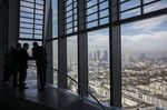 Visitors take in the city skyline view from the 15th floor pantry area inside the European Central Bank (ECB) headquarters as skyscrapers tower over commercial and residential property in Frankfurt, Germany.