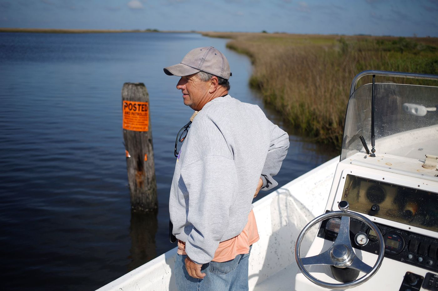 Daryl Carpenter aboard one of his fishing charter boats in the saltwater wetlands near Grand Isle, La., with a barrier erected by a private landowner.