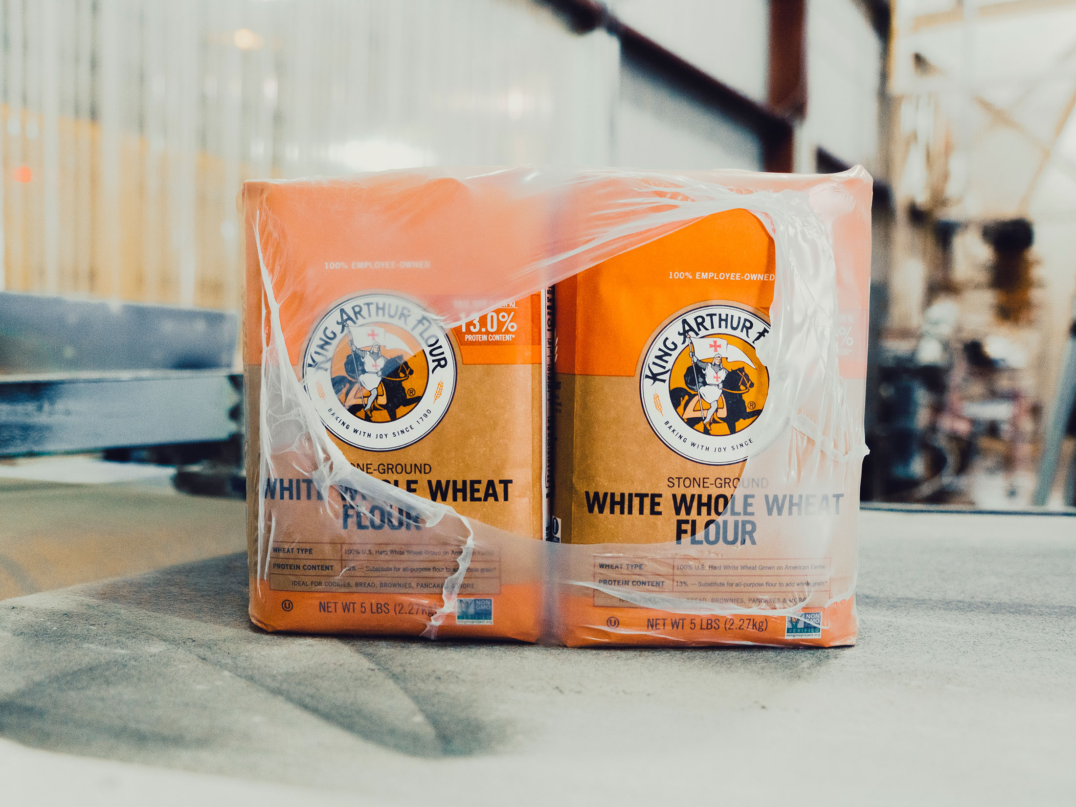 Bags of King Arthur Flour are packaged and sent along a converyor belt inside Farmer Direct Foods' flour mill in New Cambria, Kansas.