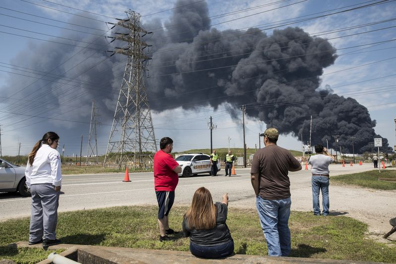 Residents look on at the plume of smoke rising from a fire at the Intercontinental Terminals petrochemical storage site in Deer Park, Texas on March 19.