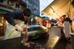 A vender cuts a tuna at a stall after the first auction of the year at Tsukiji Market in Tokyo, Japan.