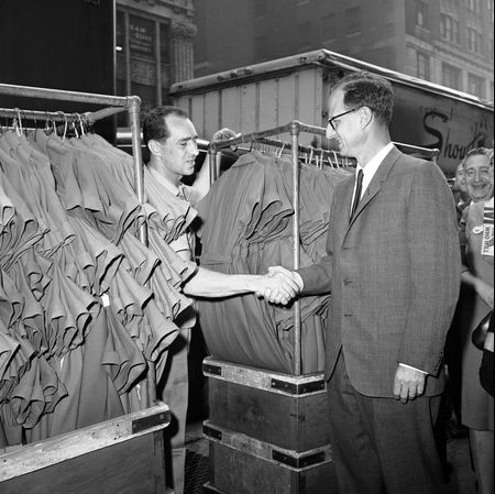 Democratic gubernatorial candidate Robert M. Morgenthau shakes the hand of a worker pushing a dolly loaded with dresses as he tours the Garment District of Manhattan in New York on Oct. 3, 1962.