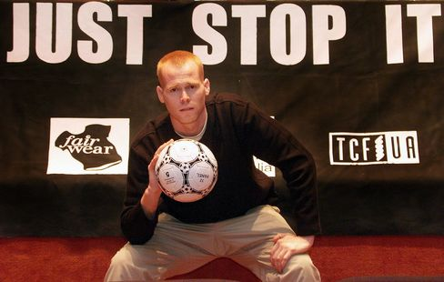 SYDNEY, AUSTRALIA:  Former American soccer pro Jim Keady sits in front of a sign playing on footwear giant Nike's 'Just Do It' slogan after Keady spent a month living in Indonesia trying to live on the wage of a Nike's workers wage of USD 1.14 per day in Sydney 04 September 2000.  The move is designed to embarrass Nike, who is a major sponsor of the upcoming Sydney 2000 Olympic Games, into providing better working conditions and pay for workers producing Nike goods.  (ELECTRONIC IMAGE) AFP PHOTO/William WEST (Photo credit should read WILLIAM WEST/AFP/Getty Images)