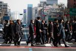 Pedestrians wearing protective masks cross a road in Seoul, South Korea, on Monday, Feb. 24, 2020.