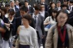Morning commuters cross a road in Tokyo, Japan, on Tuesday, May 7, 2019.